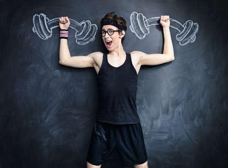 面白い弱いやつは、黒板に描かれた、重いダンベルを発生させます。スポーツ ・健康の概念。