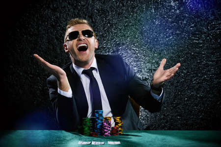 A king's ransom. Lucky  man playing cards and roulette with the excitement in casino. Gambling.