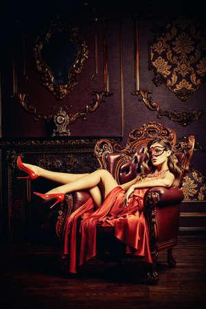 elegante mujer encantadora en vestido rojo muy bonito y la mascarada de la máscara está sentado en una silla en un apartamento de lujo. Interior clásico de la vendimia. Belleza, moda.