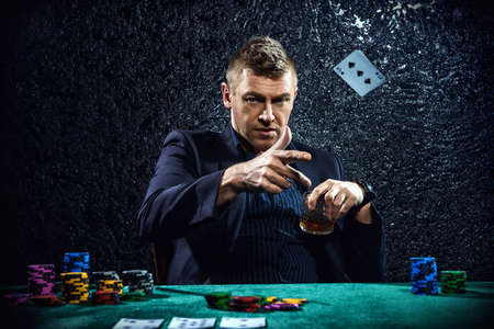 Hombre de juego emocionados tirar las cartas sobre una mesa de juego en un casino. Los juegos de azar, jugar a las cartas y ruleta. Foto de archivo - 70986876