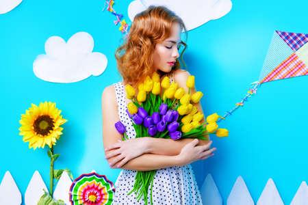 Hübsche junge Frau mit den schönen foxy Haaren hält einen Strauß Tulpen. Frühling und Sommerferien. Frauentag. Schönheit, Mode-Konzept.