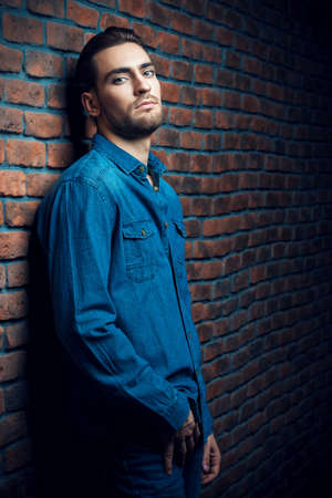 Jeans style. Portrait of a handsome young man in jeans clohes standing against the brick wall. Mens beauty, fashion. Mens barbershop, Hairstyle.