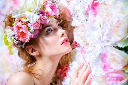 Beautiful romantic young woman in a wreath of flowers posing on a background of roses. Inspiration of spring and summer. Perfume, cosmetics concept. Stok Fotoğraf - 71198626