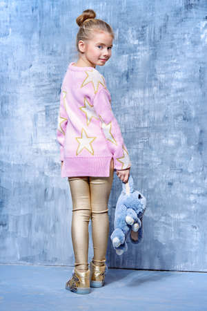 Kid's fashion. Full length portrait of a little girl with a bag like a fluffy bunny posing at studio. Easter holidays.