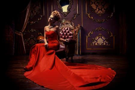 Mujer joven magnífica en vestido rojo de lujo y joyas preciosas está sentado en una silla en un apartamento de lujo. Interior clásico de la vendimia. Belleza, moda.