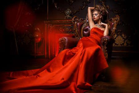 豪華な赤いドレスと貴重な宝石で壮大な若い女性は、高級マンションで椅子に座っています。クラシックなビンテージ インテリア。美容、ファッション。