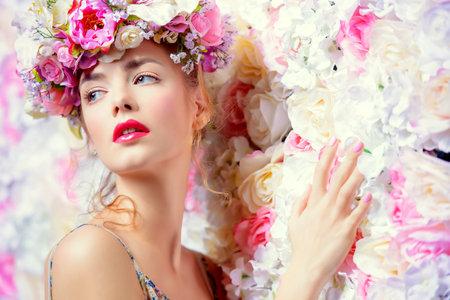 Bella romantico giovane donna in una corona di fiori in posa su uno sfondo di rose. L'ispirazione di primavera e l'estate. Profumo, cosmetici concept. Archivio Fotografico