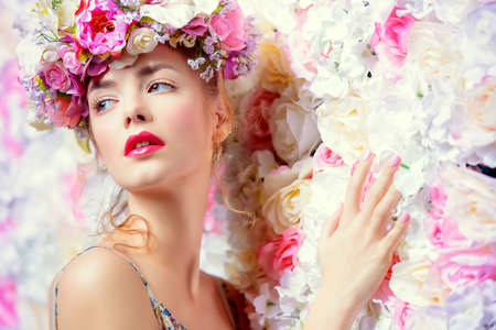 Mooie romantische jonge vrouw in een kroon van bloemen die zich voordeed op een achtergrond van rozen. Inspiratie van de lente en de zomer. Parfum, cosmetica concept. Stockfoto