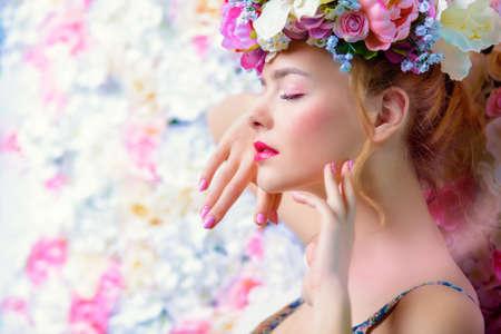 Schöne romantische junge Frau in einem Kranz aus Blumen auf einem Hintergrund von Rosen aufwirft. Inspiration von Frühling und Sommer. Parfüm, Kosmetik-Konzept.