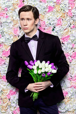 Handsome young man in an elegant suit with a bouquet of tulips over floral background. Valentines Day, Womens Day, Mothers Day. Wedding concept.