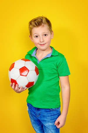 Portrait of a boy with a ball over yellow background. Healthy lifestyle. Sports and activities for children. Football.