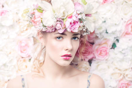 Beautiful romantic young woman in a wreath of flowers posing on a background of roses. Inspiration of spring and summer. Perfume, cosmetics concept. Stock Photo - 72019429