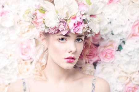 mujer joven romántica hermosa en una guirnalda de flores que presentan sobre un fondo de rosas. La inspiración de la primavera y el verano. Perfumes, cosméticos concepto.