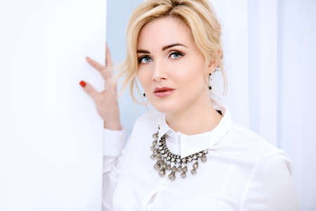 Beautiful woman with blue eyes and blonde hair wearing white blouse and necklace. Beauty, fashion concept. Luxurious lifestyle. Jewellery. Stockfoto