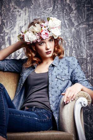 Modern young woman wearing casual jeans clothes and wreath of flowers. Cosmetics and make-up. Spring and summer fashion.