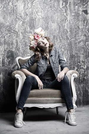 Moderne junge Frau trägt lässige Jeans Kleidung und Blumenkranz im Vintage-Sessel aufwirft. Kosmetik und Make-up. Frühling und Sommer arbeiten. Standard-Bild