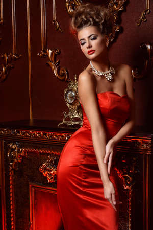 Portrait of a charming young woman in luxurious red dress and precious jewelery in a luxury apartment. Classic vintage interior. Beauty, fashion.