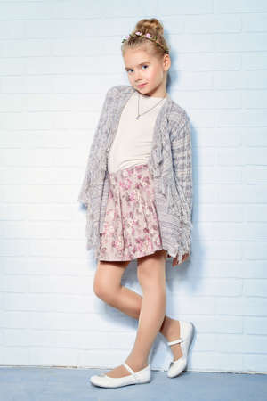 Pretty seven year old girl stands by a white brick wall and smiling. Kids fashion. Spring style.