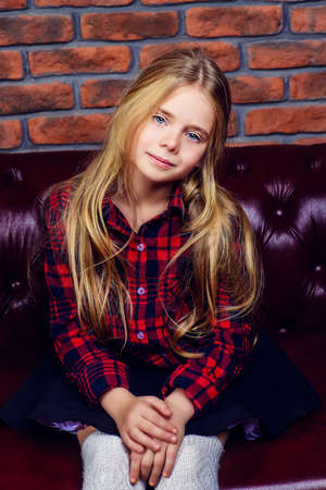 Portrait of a cute 7 year old girl in casual clothes having a rest at home. Brick wall background. Kid's fashion.