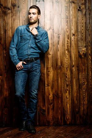 le style Jeans. Pleine longueur portrait d'un beau jeune homme en jeans clohes debout contre le mur en bois. la beauté masculine, la mode. salon de coiffure de Hommes, Coiffure.