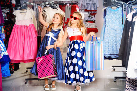 Two cute little girls go shopping. Kids fashion. Seasonal sale, shopping.