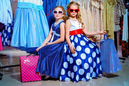 Twee schattige kleine meisjes gaan winkelen. Kindermode. Seizoensgebonden verkoop, winkelen.