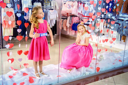 Two cute little girls in beautiful dresses posing in the window of childrens clothing store. Kids fashion. Seasonal sale and shopping.