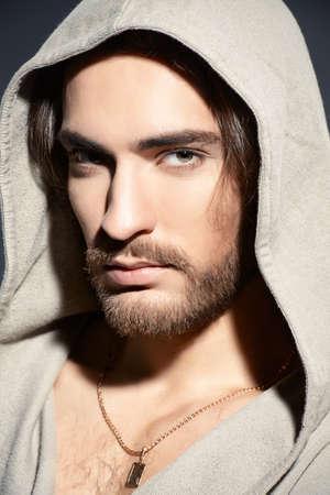 Close-up portrait of a sexy male model wearing a hooded shirt. Male beauty, fashion. Studio shot.