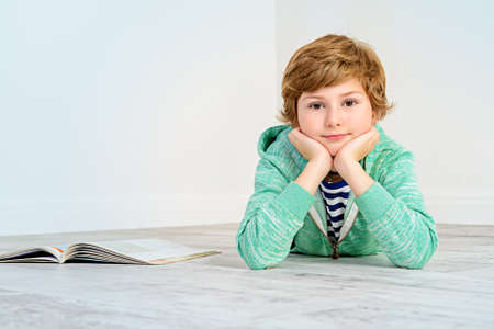 Pretty happy nine-year girl lying on a floor and smiling. Childrens fashion. Education. Activity and child concept. Copy space. Stock Photo