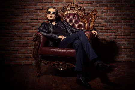Ritratto di un giovane uomo fiducioso brutale seduto rilassato in poltrona vintage costoso. Mafia, concetto criminale. Archivio Fotografico - 72800275