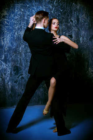 Beautiful passionate dancers dancing tango. Professional dancers. Couple in love dancing on a date. Love concept. Фото со стока