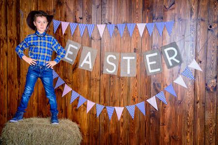 Portrait of a cute nine year old boy posing in Easter decorations. Western style, cowboy. Kids fashion. Easter. Stock Photo