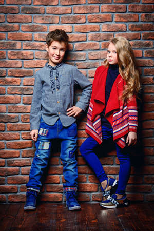 Kid's fashion. Modern nine year old boy and a girl posing at studio over brick wall background. Clothes for children.
