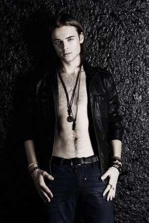 Fashion shot. Handsome sexual young man in leather jacket revealing his chest. Mens beauty.