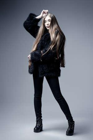 ファッションを撮影しました。黒の毛皮のコートでスタジオでポーズ美しい長い髪のファッショナブルなモデルの完全な長さの肖像画。