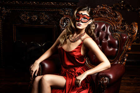 Charming elegant woman in beautiful red dress and masquerade mask is sitting in a chair in a luxury apartment. Classic vintage interior. Beauty, fashion. Stock Photo - 73432166