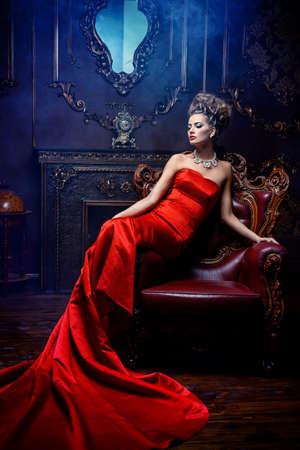 고급스러운 빨간 드레스와 귀중한 보석의 웅대 한 젊은 여자는 고급 아파트에서의 자에 앉아있다. 클래식 빈티지 인테리어. 뷰티, 패션.