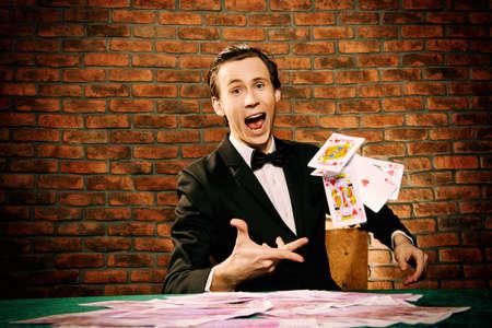 ハンサムな幸運な男がカジノのゲーム テーブルでお金を投げます。ギャンブル、トランプやルーレット。