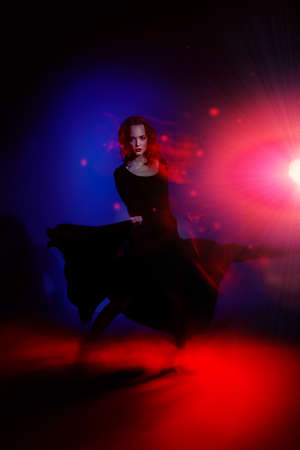 Beautiful young woman dancer performing tango at studio.