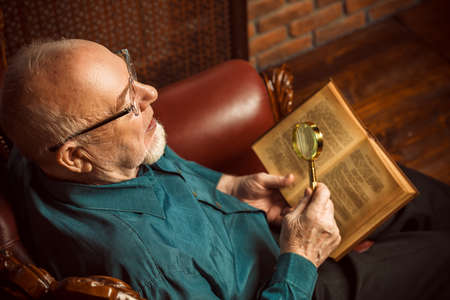 An old intelligent man reading a book in his library at home.
