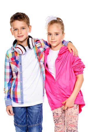 Two cute smiling children, a boy and a girl posing together in bright clothes. Isolated over white background.