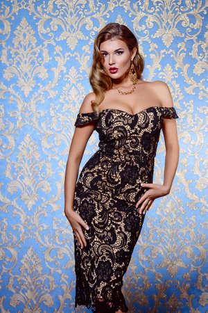 豪華なヴィンテージ背景にポーズのイブニング ドレスを着ている美しい魅力的な女性。