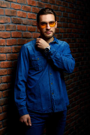 Jeans style. Portrait of a handsome young man in jeans clohes and sunglasses standing against the brick wall. Mens beauty, fashion. Mens barbershop, Hairstyle. Optics style. Stock Photo