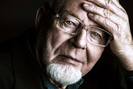 Ritratto di vecchio uomo che indossa gli occhiali. Sfondo nero. Concetto di vecchiaia.