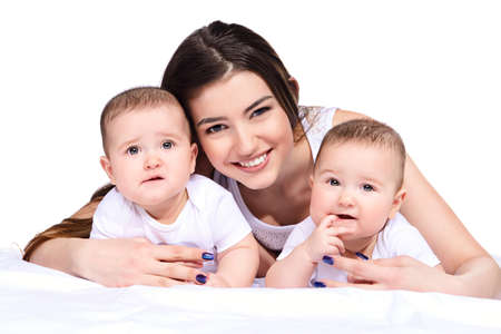 Beautiful happy mother playing with her baby children. Family concept. Healthy children. Isolated over white. Stock Photo