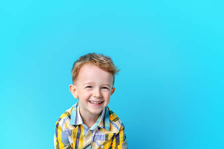 Portrait of a cute laughing little boy. Blue background. Copy space. Children fashion, summer concept.