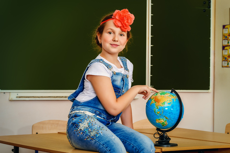 Cute schoolgirl sitting on a desk in her classroom. Education.