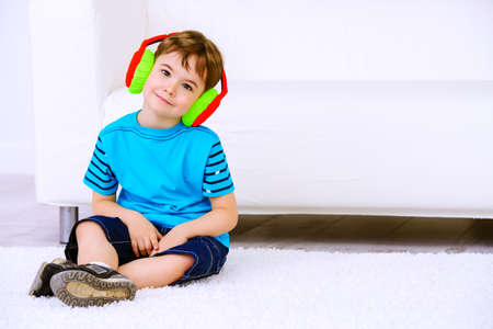 Cute little boy listens to music in headphones at home. Leisure. Family at home.