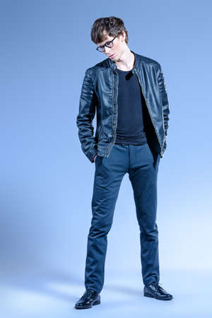 Full length portrait of a handsome young man wearing leather jacket and jeans. Male beauty, fashion. Studio shot.