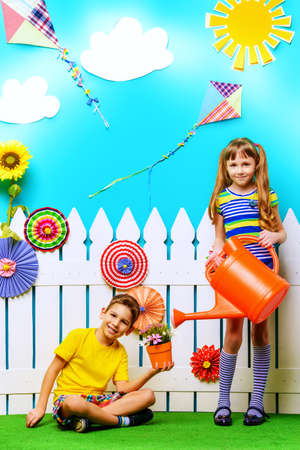 Portrait of a happy cute girl and boy posing together in summer decorations. Kids fashion. Summer style.